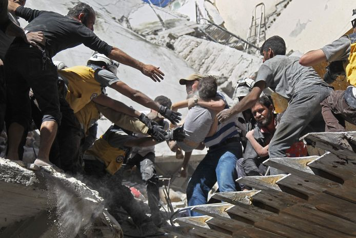 Vrijwilligers van de Witte Helmen redden burgers en kinderen uit een gebouw dat door een luchtaanval werd vernietigd in Airha, in de Syrische provincie Idlib.
