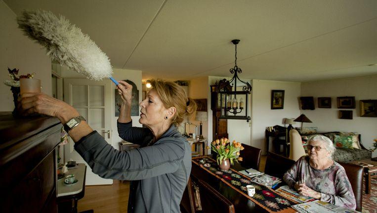 Een medewerker van Buurtzorg maakt het huis van mevrouw De Jong schoon. Beeld Anp