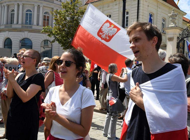 Mensen demonstreren bij het presidentiële paleis in Warschau tegen de omstreden wetten. Beeld afp