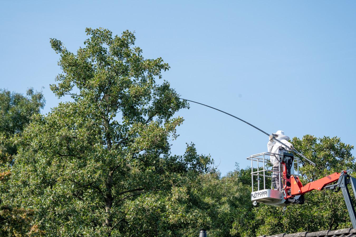 Een bestrijder gaat met behulp van een hoogwerker naar boven.