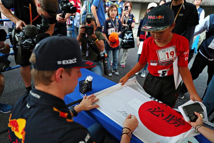 Max Verstappen zet een handtekening op een Japanse vlag.