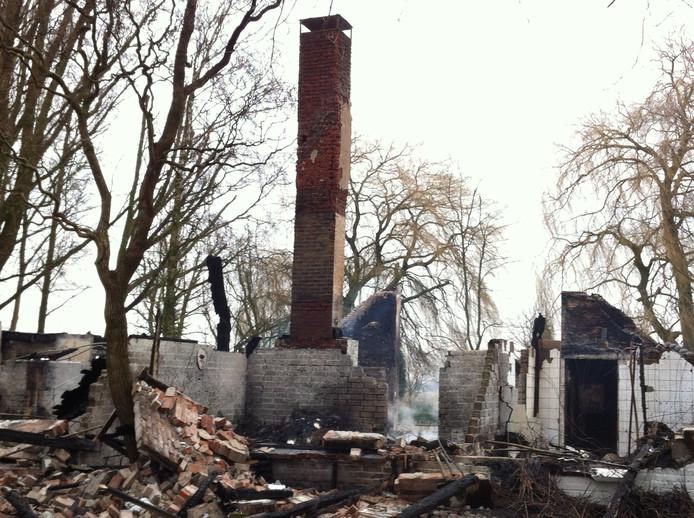 De puinhopen de dag na de brand in de woonboerderij in het buitengebied van Loo.