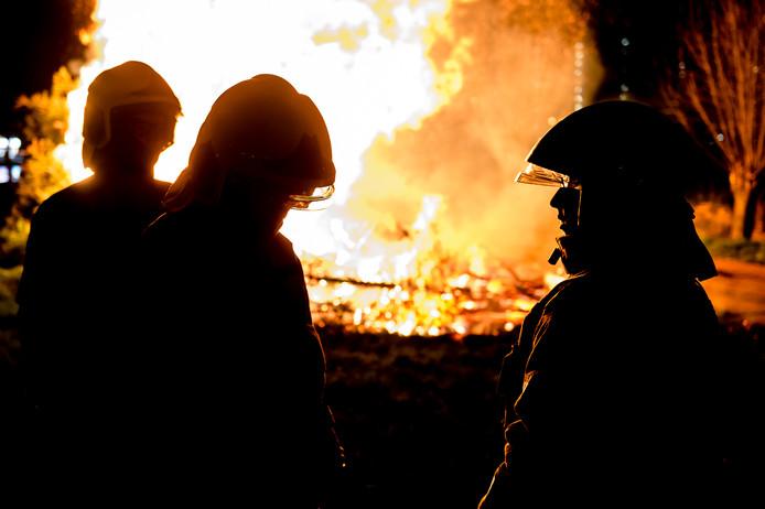 Brandweermensen bij een vuurhaard. Foto ter illustratie