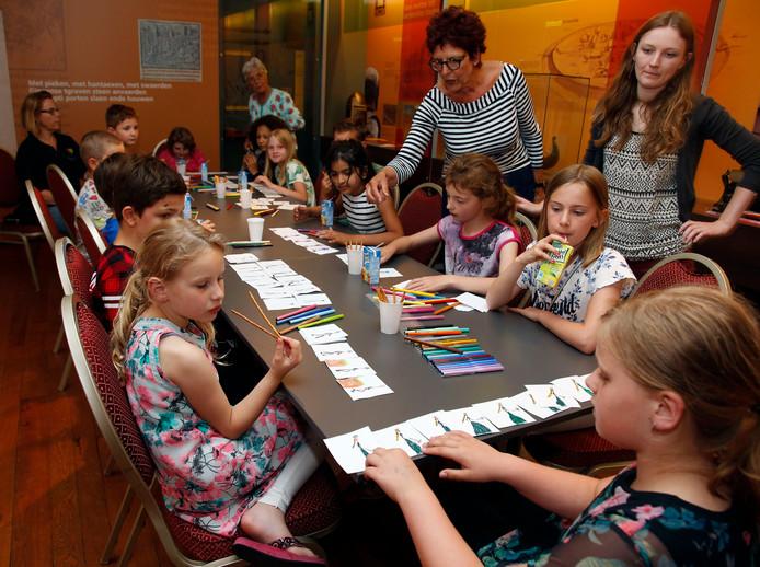 Kinderen zijn druk aan het werk in museum Het Bolwerk, onder leiding van bestuurslid Anne-Lies Soet (midden) en docente Anne Nobels (rechts).