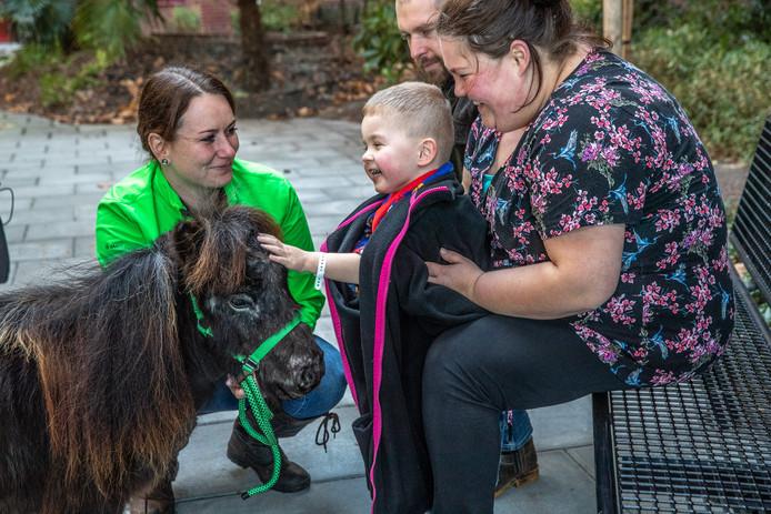Moeder Debby Wessels (rechts) laat haar zoon Jim (3) even ontsnappen aan de ziekenhuismuren en knuffelen met een shetlandpony.