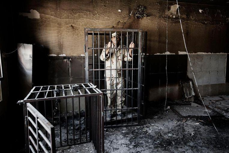 Een militair demonstreert in Falluja hoe strijders van Islamitische Staat gevangenen opsloten in kooien van verschillende afmetingen. Beeld Daniel Rosenthal / de Volkskrant