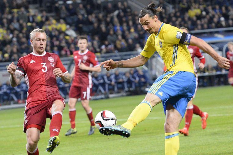 De Deense verdediger Simon Kjaer (L) reageert als Zlatan Ibrahimovic (r) een schot lost tijdens de wedstrijd tussen Zweden en Denemarken in Solna. Beeld afp