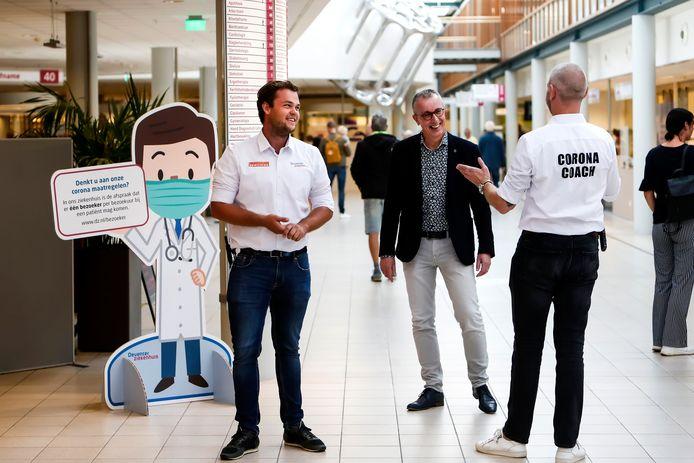 Coronacoaches Nordwin (links) en Ton (rechts) in gesprek met front office manager Henk Kleine Schaars.