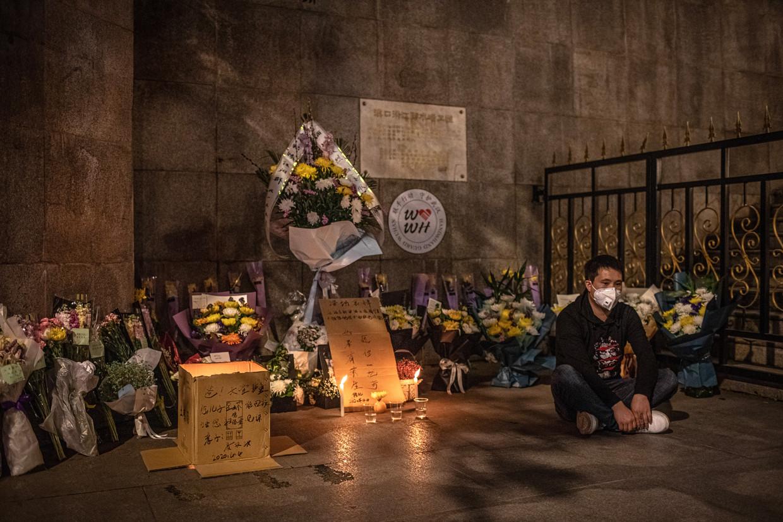 Een man zit naast een herdenkingsplek voor slachtoffers van Covid-19.