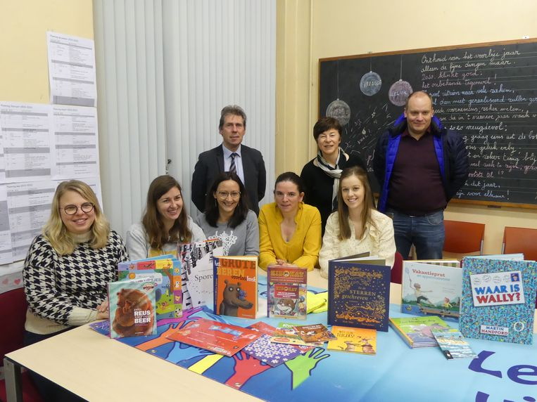 De leerkrachten en directeur Franky De Graeve van basisschool Leieparel kregen een boekenpakket van David Vanhee van VCOV.