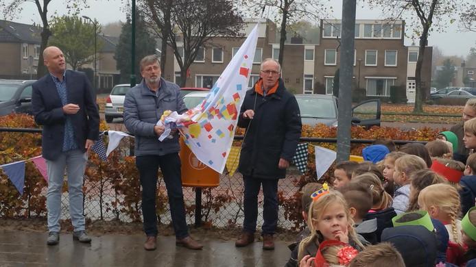 De langst zittende meesters Jan van Sluisveld (rechts) en Peter van den Broek hijsen de feestvlag. Links directeur Joris Dekker.
