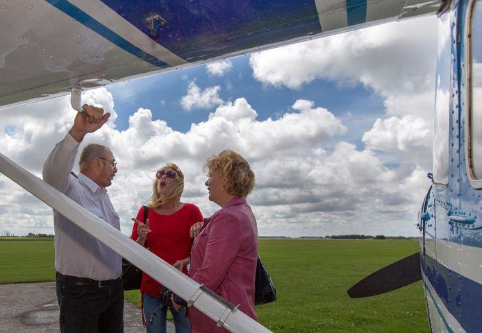 Vlnr: Piloot Hans van der Linden geeft aan twee passagiers uitleg over zijn Cessna op vliegveld Midden Zeeland.