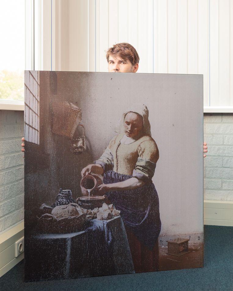 Een werknemer van Kameleon Solar houdt zonnepaneel met daarop de afbeelding van 'Het Melkmeisje' van Vermeer vast.  Beeld Pauline Niks