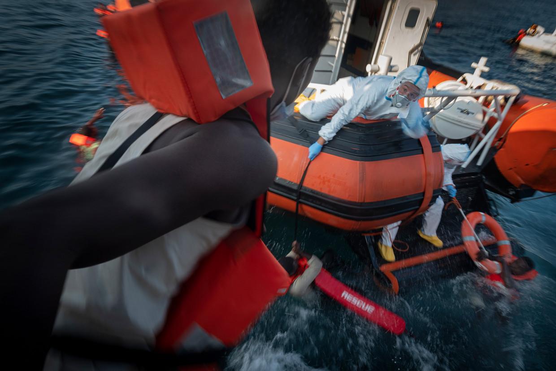 Migranten springen vanaf het dek van het schip van de Spaanse organisatie Open Arms in zee, ten zuiden van Sicilië. Beeld AP