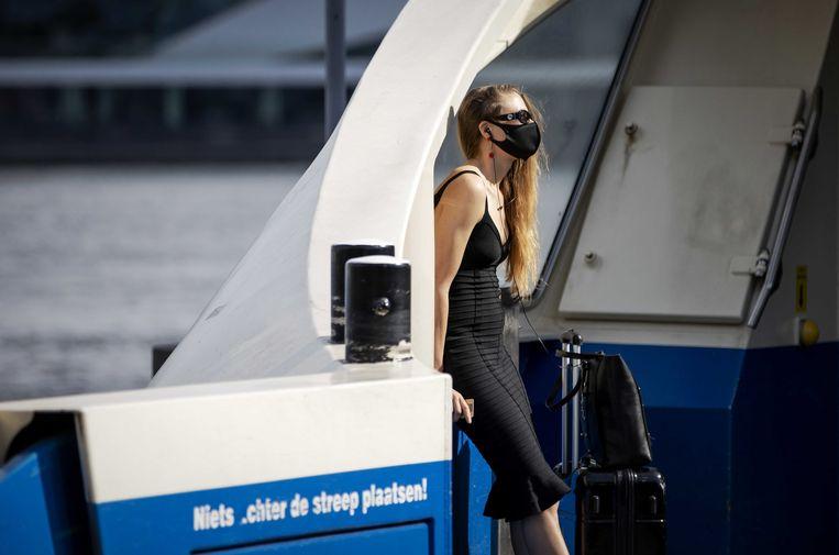 Reizigers met mondkapjes bij de pont achter Amsterdam CS.  Beeld ANP
