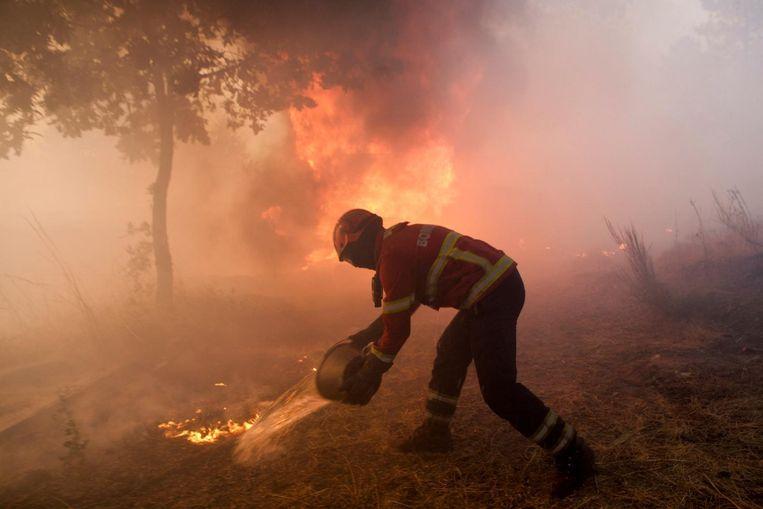 Een brandweerman gooit water op het vuur in de buurt van de plaats Trancoso, in het noorden van Portugal