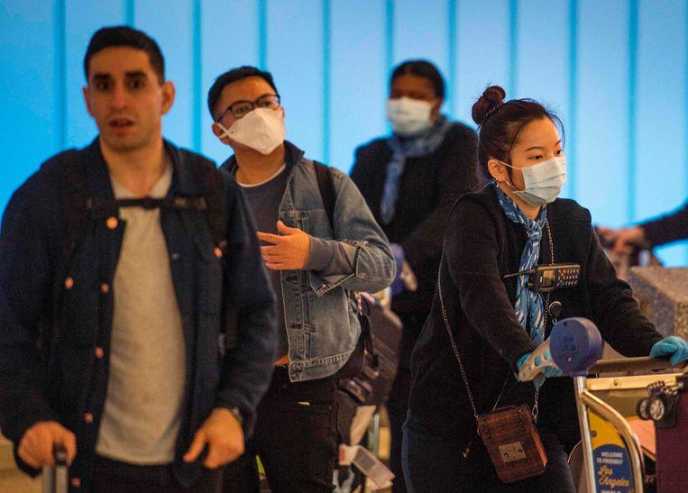 Op vliegvelden wereldwijd, hier op Los Angeles International Aiport, dragen passagiers mondkapjes ter bescherming tegen het nieuwe coronavirus  Beeld AFP
