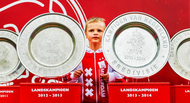 Een jonge Ajax-fan in 2014 tussen de kampioensschalen van Ajax. Beeld anp