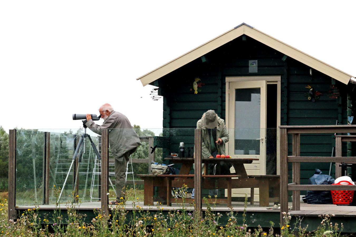 Piet van Iersel kijkt met zijn verrekijkers naar vogels in de Biesbosch vanaf een huisje op de natuurcamping De Knotwilg in Werkendam.