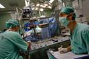 Twee artsen tijdens een vitale hartoperatie. De een houdt op een scherm de lichaamsfuncties in de gaten, de ander bedient de hart-longmachine.