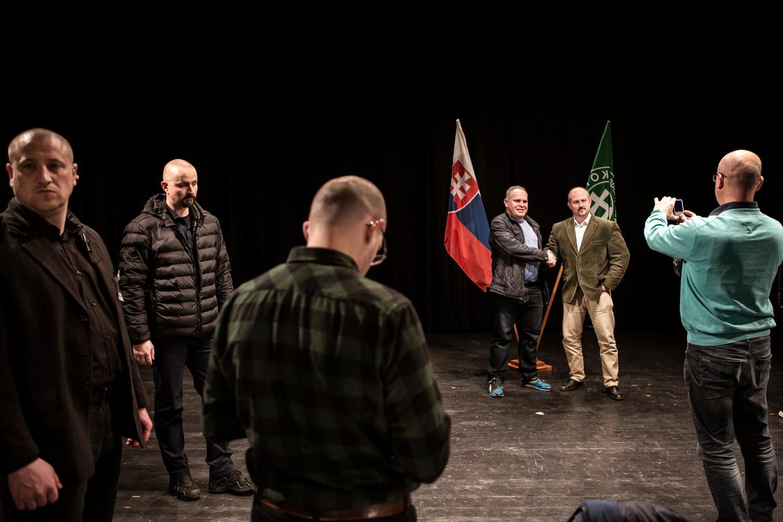 Kotleba (groen colbert) gaat in Ruzomberok op de foto met aanhangers. Beeld Julius Schrank / De Volkskrant