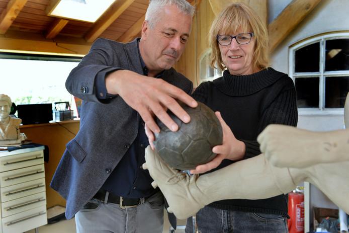 Jean-Paul Decossaux kijkt samen met kunstenares Lia Krol naar haar beeld in wording van Dennis Bergkamp. Dat blijft nog tot de onthulling van het bronzen eindresultaat buiten beeld.