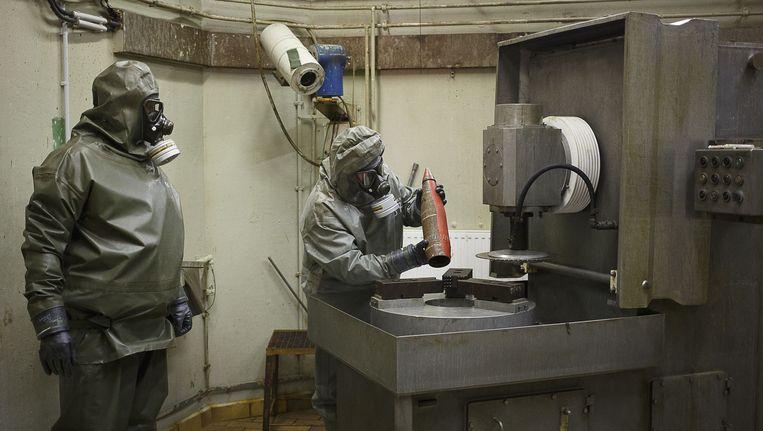 Medewerkers van OPCW oefenen het ontmantelen van een chemisch wapen in een ontmantelingslab in Duitsland. Beeld AFP