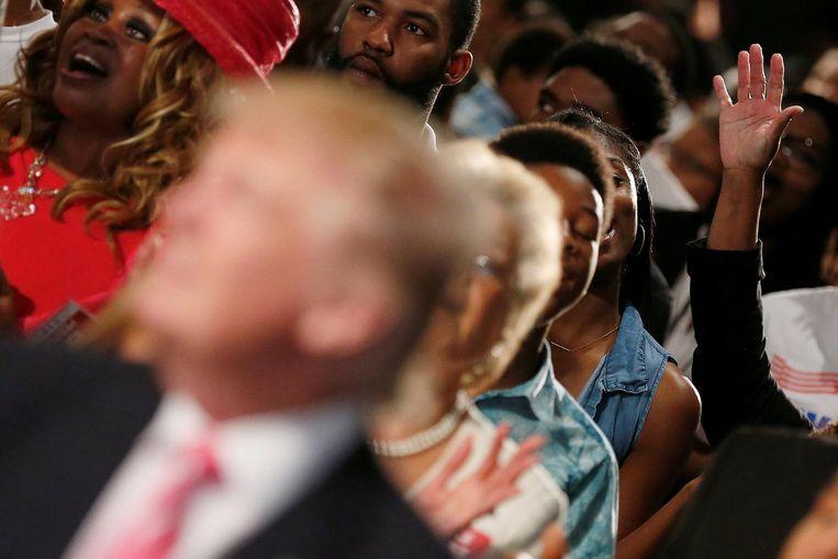 Trump tussen de zingende kerkgangers in Detroit. Beeld reuters