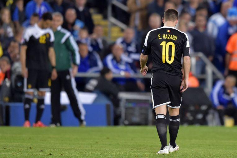 Eden Hazard trekt met het hoofd naar beneden naar de kant. Chadli is zijn vervanger.