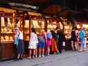 Toeristen kijken naar etalages van sieradenwinkels op Ponte Vecchio.