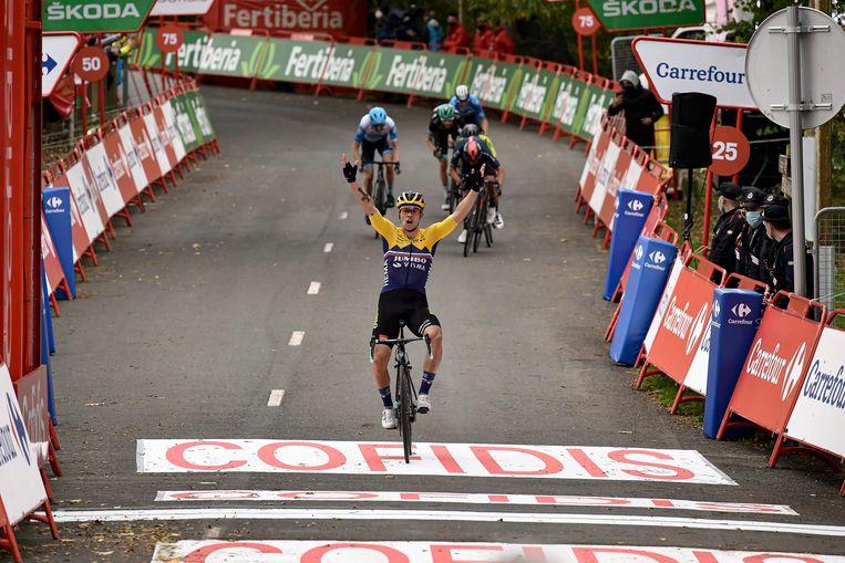 Terwijl zijn medevluchters sprinten om de de tweede plaats, komt Primoz Roglic juichend over de finish van de eerste etappe van de Vuelta. Beeld AP