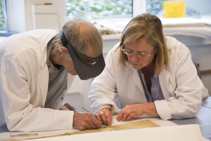 restaurateurs buigen zich over een eeuwenoud document en proberen het in ere te herstellen