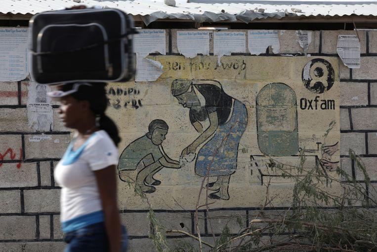 Een vrouw loopt langs een muurschildering van Oxfam in Corail, een kamp voor mensen die hun huis verloren zijn na de aardbeving in 2010 op Haïti. Beeld REUTERS