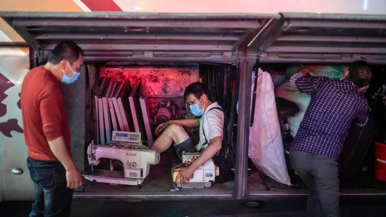 Een arbeidsmigrant die in Guangzhou (de hoofdstad van Guangdong) niet meer aan de slag kan, wurmt zich met zijn naaimachines in de bus op weg naar zijn geboorteprovincie Hubei.