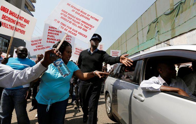 Een politieman in de Keniaanse hoofdstad Nairobi verhindert dat demonstrerende taxichauffeurs passagiers uit een auto van Uber trekken. Beeld reuters