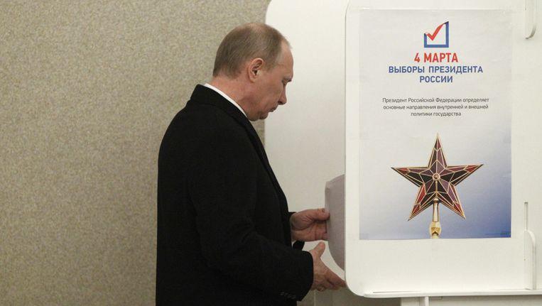 De Russische premier - en presidentskandidaat - Vladimir Poetin brengt zijn stem uit. Beeld ap