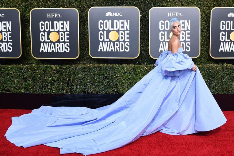 Lady Gaga koos voor een blauwe jurk met een enorme sleep en bijpassend blauw haar.