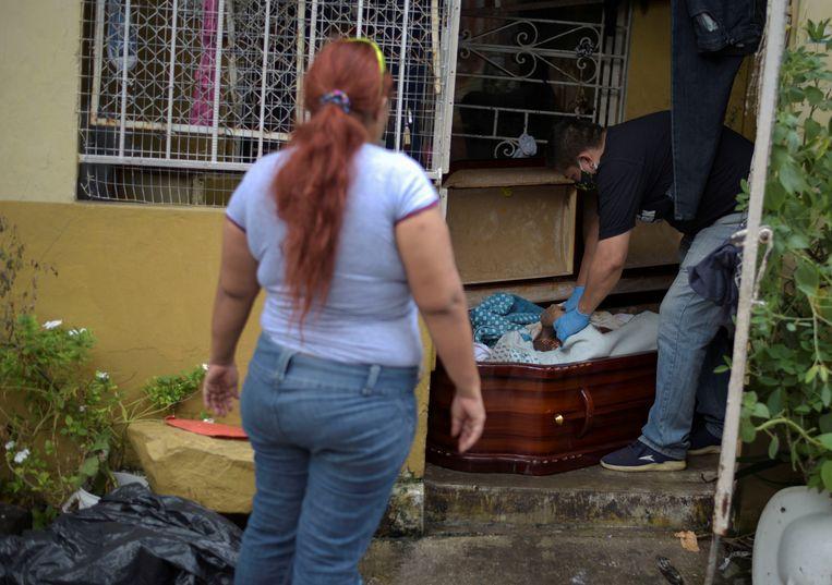 Een vrouw ziet haar moeder opgehaald worden die een dag eerder thuis is overleden. Beeld Reuters