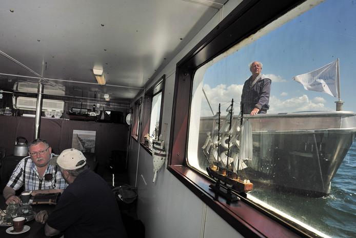 Weervisser Cor van Dort (rechts) komt langszij van de rondvaartboot met nazaten van weervisserfamilies. (Archieffoto)
