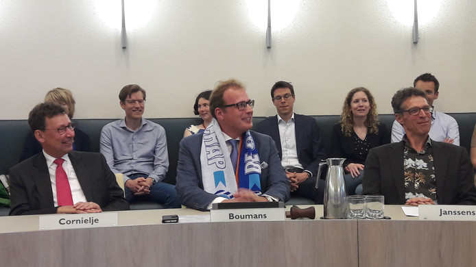 Mark Boumans luistert, met Orion-sjaal én Graafschap-sjaal, naar de toespraken tijdens zijn installatie als burgemeester van Doetinchem. Links van hem Commissaris der Koning Clemens Cornielje, rechts de Doetinchemse griffier Rob Janssens.