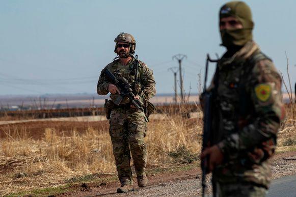 Een Amerikaanse soldaat (L) en een lid van de YPG in de Noord-Syrische stad al-Malikiyah (Derik) aan de grens met Turkije eergisteren.