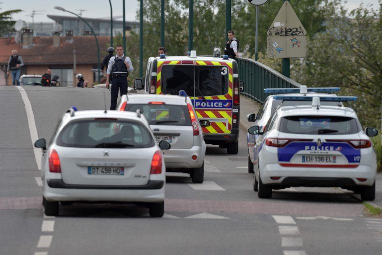 Agenten op de plek waar een gewapende man vier personen gegijzeld houdt. Beeld AFP