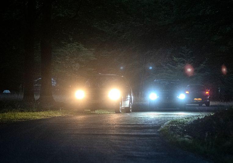 Auto's rijden op een weg op de Veluwe die afgesloten is tussen zonsondergang en zonsopkomst.  Beeld Koen Verheijden