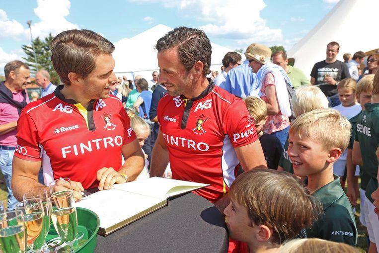 Red Lions Vincent Vanasch en Sebastien Dockier ondertekenen het gulden boek voor de opening van het kunstgrasveld.