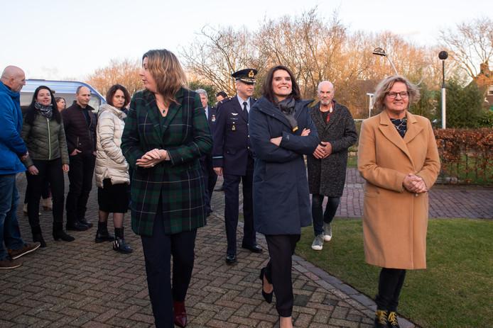 Karin Kolen (rechts) en echtgenoot Cees, schuin achter haar, loopt samen met staatssecretaris Visser en wethouder Sandra Diepstraten naar hun woning in Hulten. Rechts op de achtergrond een van de microfoons die het geluid meten dat vliegtuigen en helikopters van vliegbasis Gilze-Rijen veroorzaken.