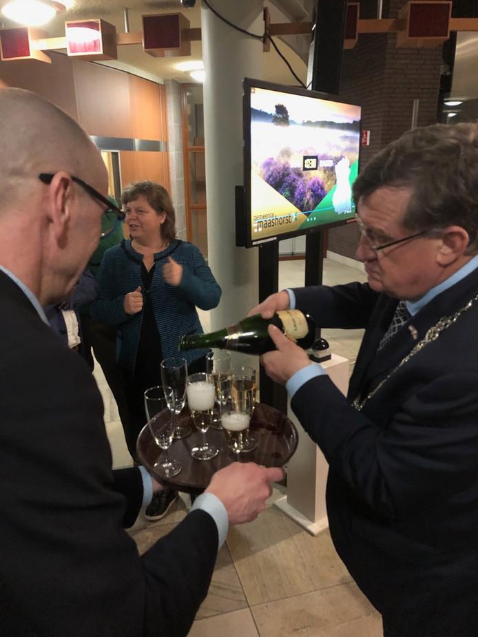 Burgemeester Henk Hellegers schenkt champagne na afloop van het fusiedebat in Uden. Op de achtergrond het scherm in de publiekshal dat aangeeft dat het nog 1038 dagen is tot 1 januari 2022.