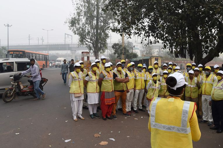 Volunteers from civil defence get ready to monitor vehicles after the local government ordered half of the city's private cars to be taken off the road based on an odd-even registration plate system to help reduce air pollution, in New Delhi on November 4, 2019. - Millions of people in India's capital started the week on November 4 choking through