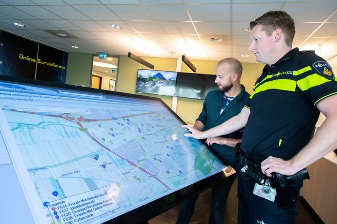 Tom Slijpen (l) en Simon Leijten overleggen bij de beeldtafel over verschillende vormen van cybercrime en zoomen in op Waalwijk.