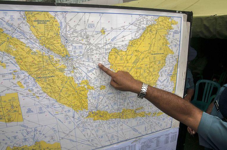 Een Indonesische luchtvaartbestuurder toont journalisten in Surabaya (Oost-Java) een kaart van het zoekgebied. Beeld afp
