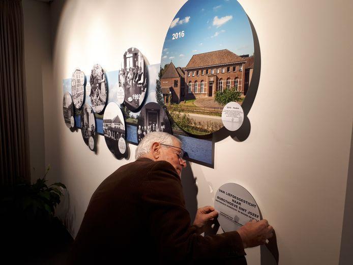 Lambert van den Berg hangt het laatste paneel van het kunstwerk op in de centrale hal van Sint Jozef in Oijen.